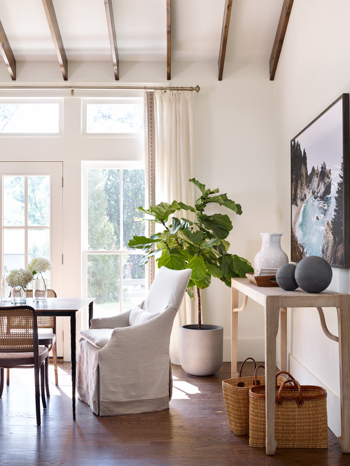 Chic dining room with a sloped ceiling accented with rustic wood beams over  a sleek legged dining table lined with cane back dining chairs as well as  ...