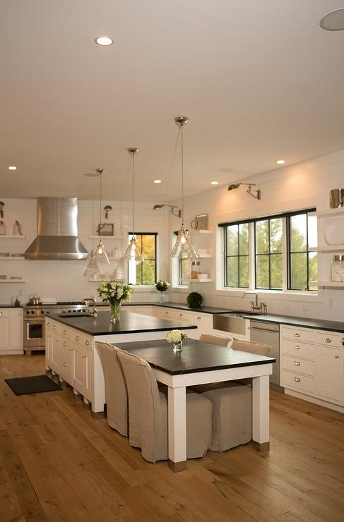 two glass cone shaped pendants hang over a white kitchen island topped with soapstone fitted with a prep sink next to a dropdown soapstone top dining table