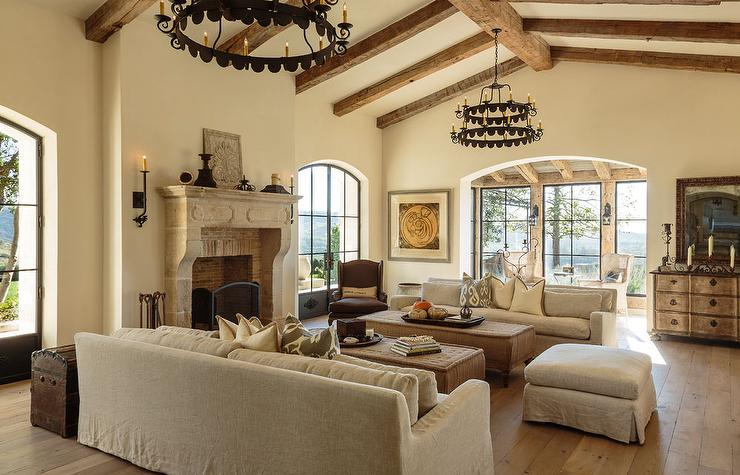 Mediterranean Living Room Features Cathedral Ceilings Accented With Rustic  Wood Beams And Tiered Iron Candelabras Illuminating A Large Stone Fireplace  With ... Part 13