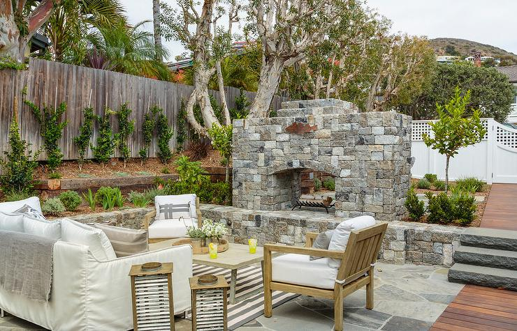 Sunken Patio Is Filled With A White Slipcovered Outdoor Sofa Facing A Gray  Outdoor Coffee Table And Teak Accent Chairs Facing A Stone Fireplace.