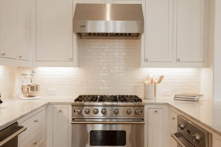 Attractive Chic Kitchen Features White Shaker Cabinets Paired With Carrera Marble  Countertops And A White Glazed Mini Subway Tiled Backsplash.
