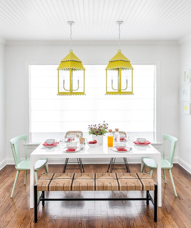 Contemporary Dining Room Features Two Yellow Lanterns Illuminating A White  Modern Dining Table Lined With Wicker Dining Chairs Facing A Wicker Bench  As Well ...