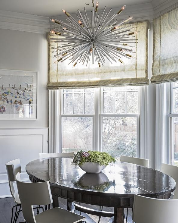 Contemporary Dining Room Features A White And Gold Sputnik Chandelier Hanging Over An Oval Glossy Wood Table Lined With T Back Chairs