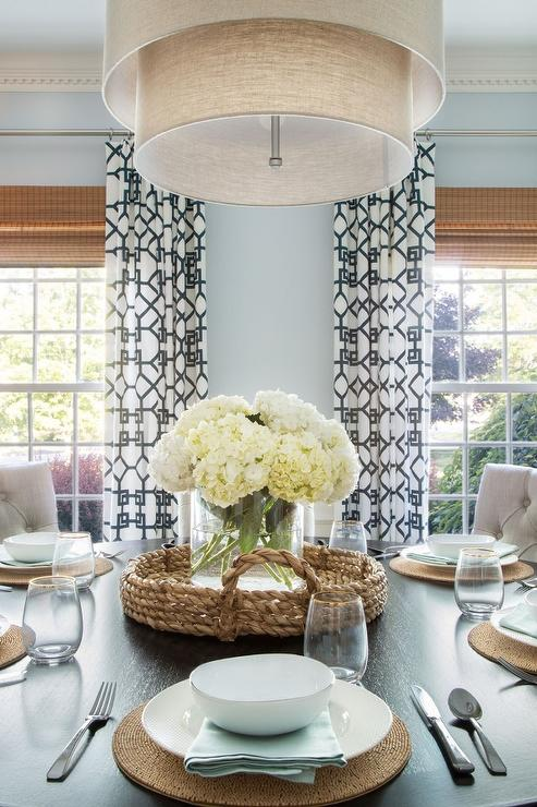 Gorgeous Dining Room Features A Dark Stained Table Lined With Beige Tufted Chairs Illuminated By Tiered Drum Pendant