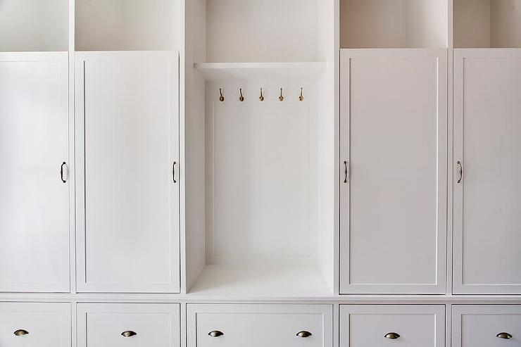 Classic white mudroom features a row of cubbies above closed mudroom ...