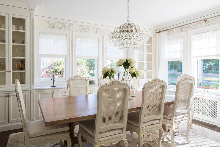 Chic French Dining Room Features A Crystal Droplets Chandelier Suspended Over Walnut Table Lined With White Cane Chairs Atop