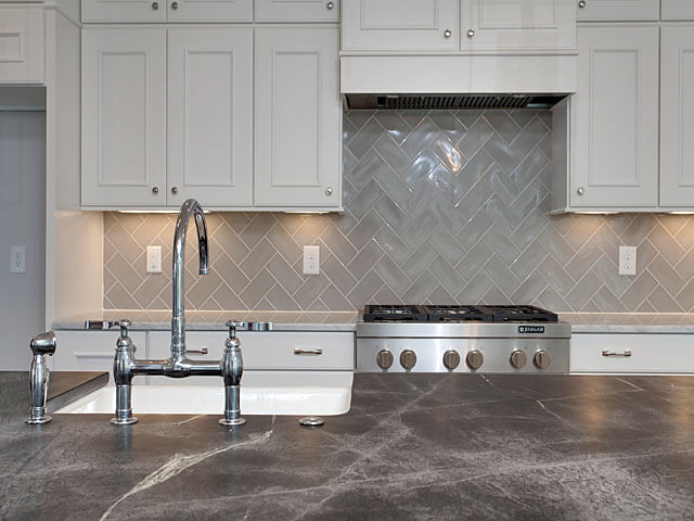 Lovely Kitchen Features A Center Island Topped With Soapstone Fitted With A  Farmhouse Sink And A Deck Mount Gooseneck Faucet.
