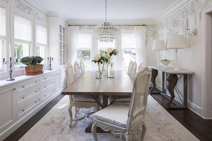 Chic Dining Room Features A Crystal Droplets Chandelier Suspended Over A  Walnut Dining Table Lined With White French Cane Dining Chairs Atop A White  And ...
