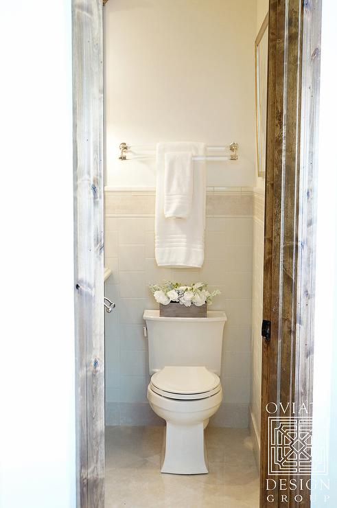 Lovely bathroom boasts a lucite and brass double towel holder placed over  toilet. Towel Rack Above Toilet Design Ideas