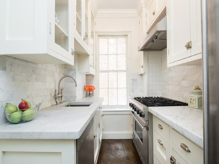 small white galley kitchen with sink across from stove