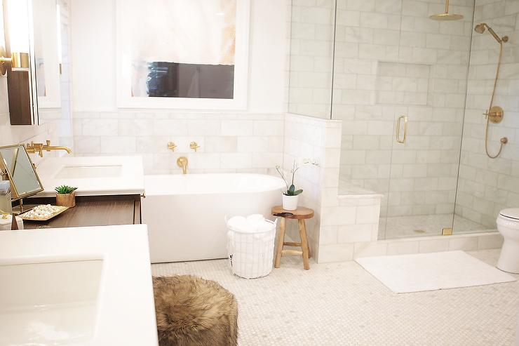 a glass and brass shower enclosure is filled with marble tiles lined with a kohler rainhead with katalyst spray in vibrant moderne brushed - Kohler Tub