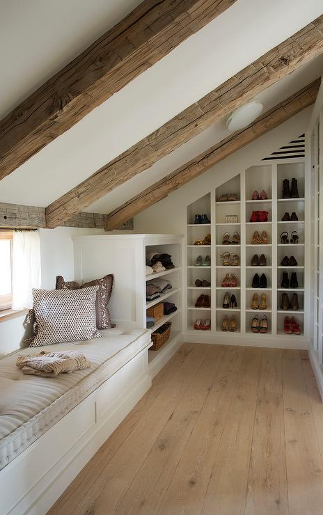 Walk in attic closet features a sloped ceiling lined with rustic wood beams  over angled built in shoe cubbies and sweater shelves next to a window seat. Attic Bathroom Sloped Cieling Design Ideas