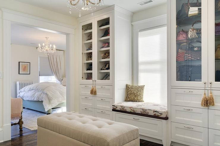 Truly gorgeous closet boasts a built-in window seat flanked by glass ...