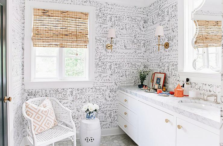 Pencil & Paper - Chic black and white bathroom boasts walls clad in Saul Steinberg Aviary Wallpaper lined with a white floating vanity adorned with brass ...
