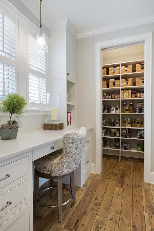 Long And Narrow Kitchen Pantry Features A Built In Desk, Placed Below  Windows Dressed In Plantation Shutters, Paired With A Beige Tufted Stool  Atop Rustic ...