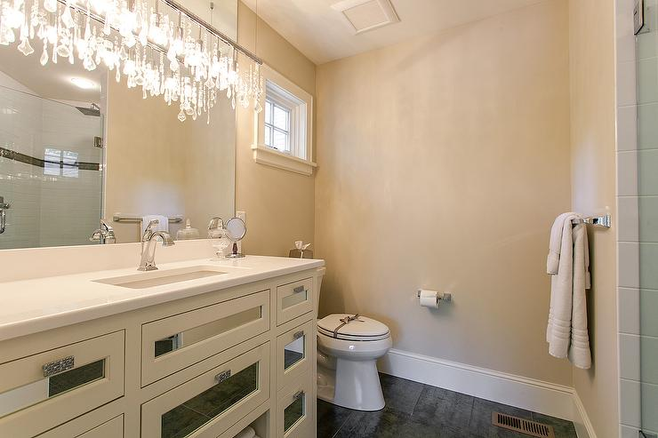 White crystal chandelier design ideas fabulous powder room boasts a crystal linear chandelier hanging over a white washstand with mirrored drawers alongside a gray tiled floor aloadofball Image collections
