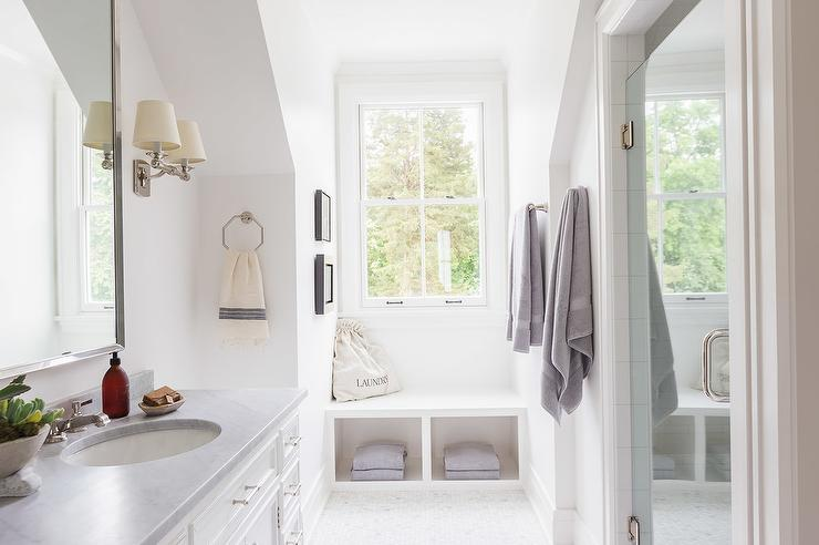 Alyssa Rosenheck   White bathroom features a sloped ceiling nook filled with a white washstand topped with a gray counter under a beveled mirror illuminated. Bathroom Window Seat Design Ideas