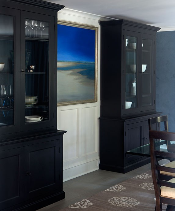 Chic Dining Room Features Tall Black China Cabinets