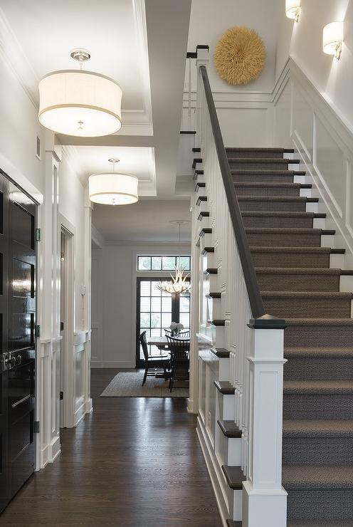 Exceptionnel Chic, Long Foyer Features A Glossy Black Paneled Closet Door Facing A  Staircase Illuminated By White Drum Pendants With Ribbon Trim.