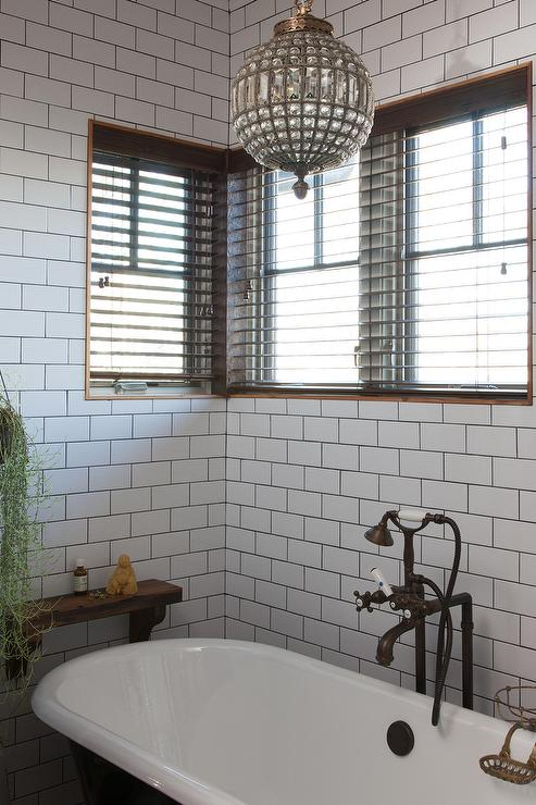 Black claw foot tub with 19th c casbah crystal chandelier - White subway tile with black grout bathroom ...