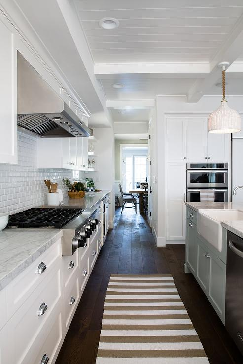 Stunning Kitchen Features A White Cabinets Paired With Gray And White  Marble Countertops And A White Mini Beveled Subway Tile Backsplash.