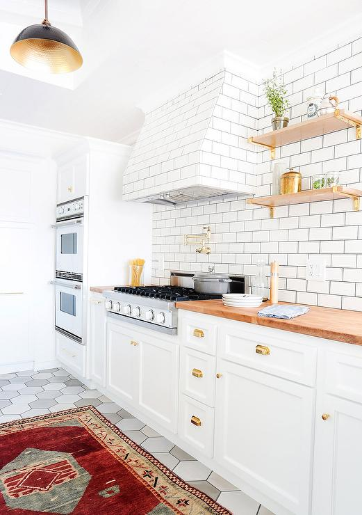 White Kitchen Cabinets With Brass Cup Pulls And Butcher