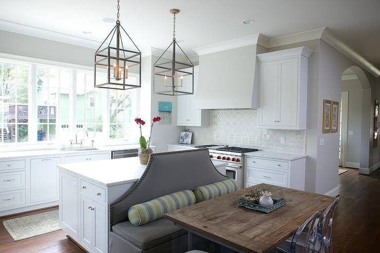 ... Lanterns Hang Over A Kitchen Island Fitted With A Gray Banquette Lined  With Yellow And Gray Bolster Pillows Facing A Reclaimed Wood Top Dining  Table ...