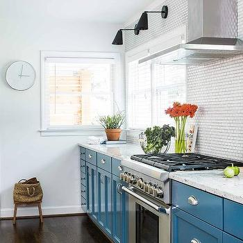 Contemporary kitchen features blue base cabinets paired with white