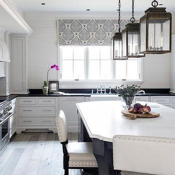 black curved kitchen island with white marble countertop