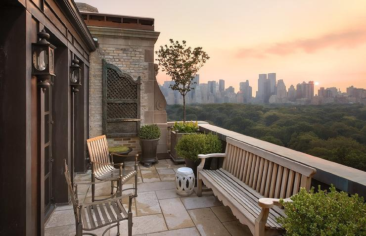 Balcony with teak bench and wrought iron chairs for Central park apartment new york