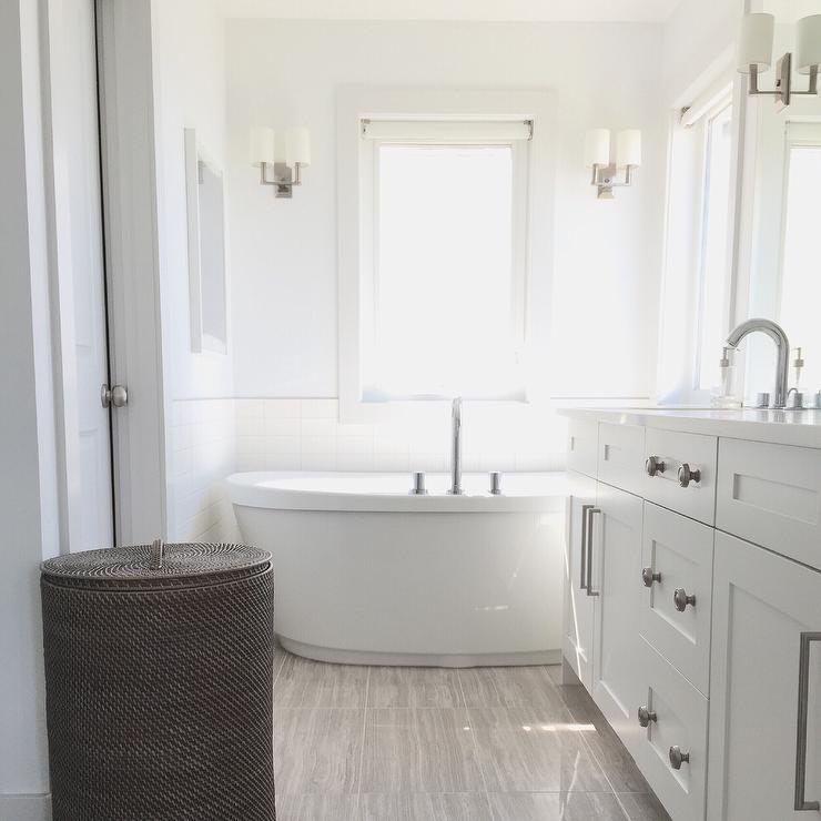 Lovely Bathroom Features A White Dual Washstand Topped With Quartz Placed Next To An Oval Freestanding Tub Atop Light Gray Wood Like Tiled Floors