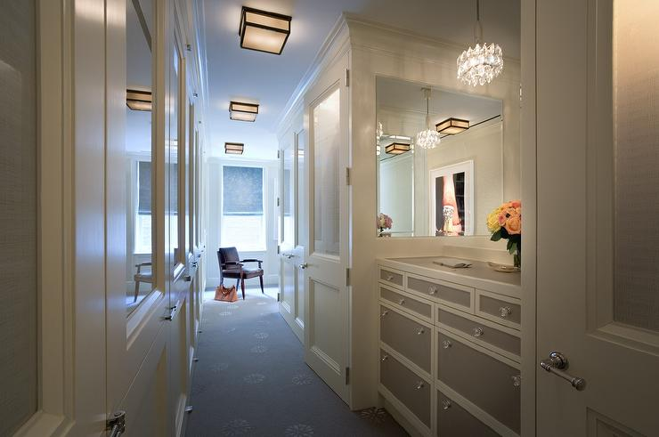 Chic, Long Closet Features A Built In White And Gray Dresser Adorned With  Glass Knobs Placed Under Mirrors Lit By A Crystal Chandelier.