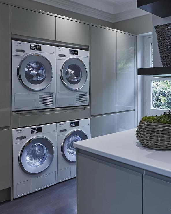 gray lacquered laundry room cabinets with two sets of washers and