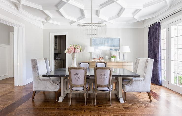 Chic Dining Room Boasts A Geometric Coffered Ceiling Accented With An Oval Fringe Chandelier Illuminating Zinc Top Trestle Table Lined Purple