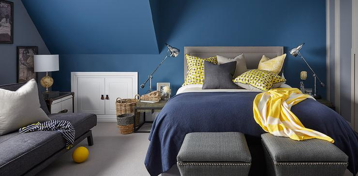 Yellow  gray and blue bedroom features walls painted blue lined with a gray  nailhead headboard on bed dressed in a blue blanket as well as yellow and  gray. Gray Bedroom With Yellow Sofa Design Ideas