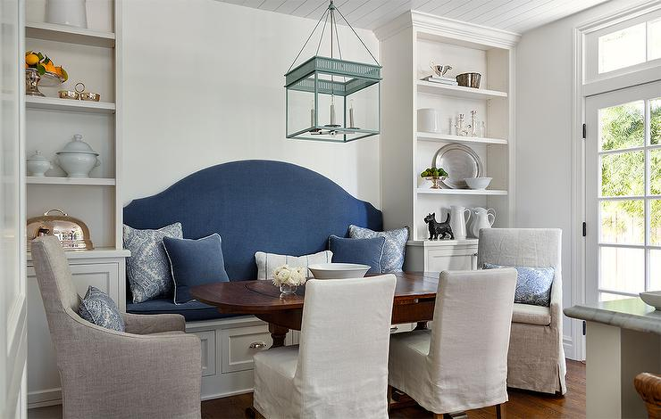 Cottage Breakfast Room Boasts A Built In Bench Lined With Blue Seat Cushion And Curved Upholstered Back Flanked By Floor To Ceiling Shelving Units