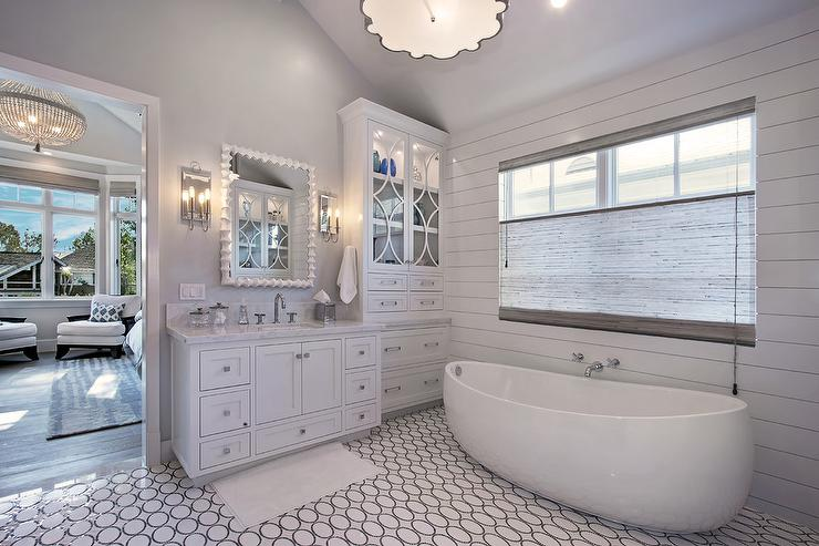 White and gray bathroom features a shiplap clad accent wall lined with a  tub filler over an egg shaped tub atop a white and gray oval tiled floor. Bathroom Shiplap Accent Wall Design Ideas