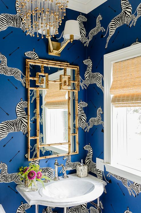 blue powder room with gold bamboo mirror