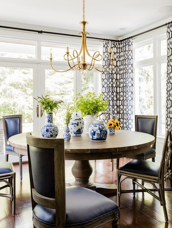 Round Dining Table And Black French Chairs With Double Twist Large Chandelier