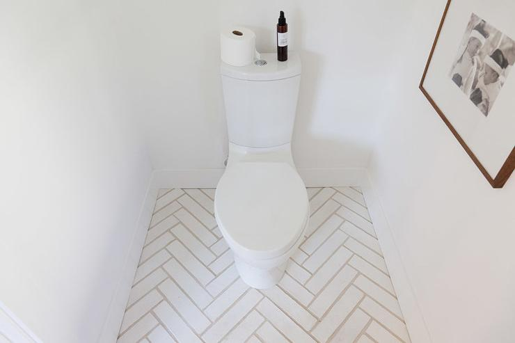 modern white bathroom boasts a nook filled with a toilet atop a white