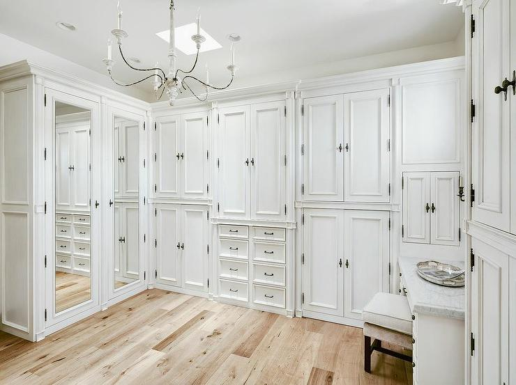 French White Closet Features A Small Skylight Illuminating