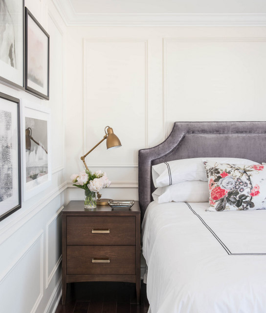 elegant bedroom features a wall accented with trim moldings lined with