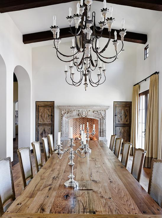 Features A Long Plank Dining Table Lined With French Linen Chairs Illuminated By Candle Chandeliers Placed In Front Of Stone Fireplace