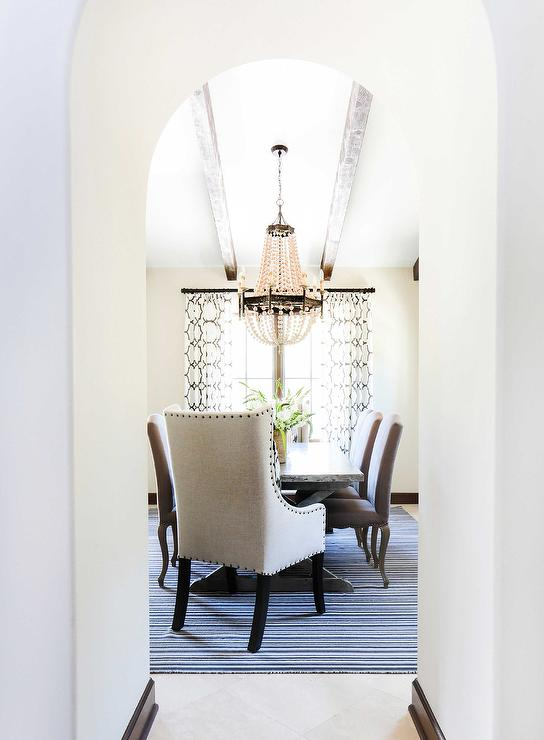 beautiful dining room features a vaulted ceiling accented with a regina andrew scalloped wood bead chandelier a zinc top dining table lined - Wood Bead Chandelier