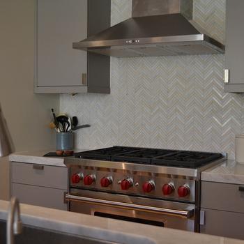 gray flat front cabinets with white iridescent herringbone tile backsplash - Backsplash Design Ideas