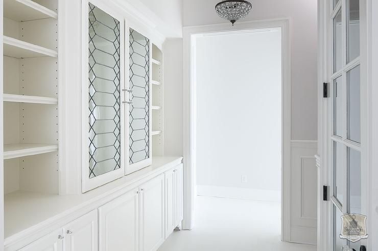 walk in closet with leaded glass cabinet doors