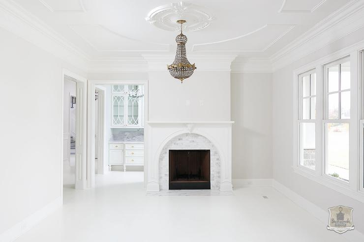 Beautiful white living room features a French empire beaded chandelier illuminating a white fireplace accented with a curved marble surround.
