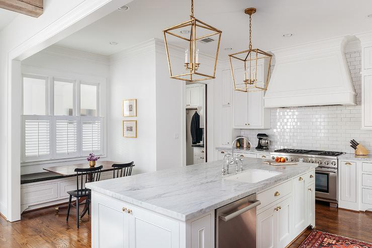 A Pair Of Antique Brass Darlana Lanterns Hang Over A White Kitchen Island  Topped With Marble Fitted With A Sink And Deck Mount Faucets Lined With  Backless ...