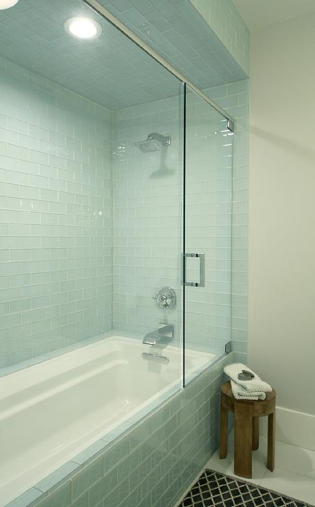 bathroom glass tile tub. Fabulous bathroom features a drop in tub shower combo tiled turquoise  glass subway tiles alongside pot lighting and square rain head Turquoise Blue Glass Tiles Design Ideas