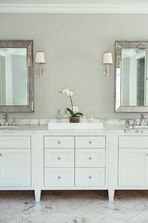 Lined With A White Footed Dual Vanity Topped Gray And Marble Fitted His Hers Sinks Placed Under Rectangular Beaded Beveled Mirrors